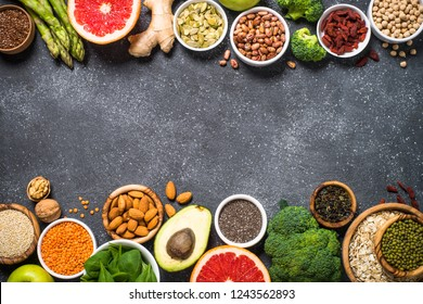 Superfoods on black stone background. Organic food and healthy vegan food. Legumes, nuts, seeds, fruit and vegetables. Top view copy space.