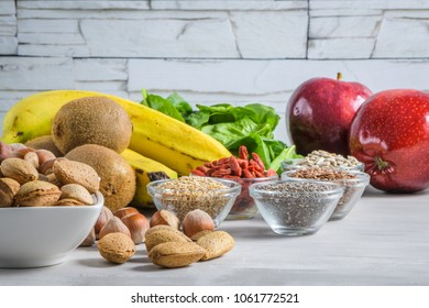 Superfoods on a gray background with copy space. Nuts, beans, greens and seeds. Healthy vegan food.