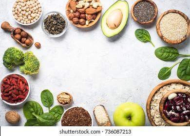 Superaliments sur fond gris avec place pour copie. Noix, haricots, verts, fruits et graines. Nourriture végétalienne saine.