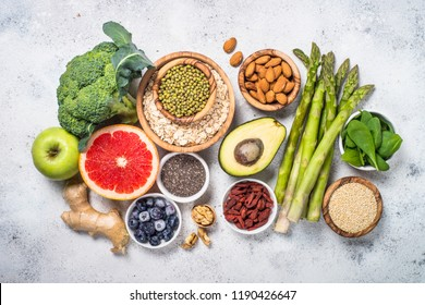 Superfoods on light stone background. Organic food and healthy vegan food. Legumes, nuts, seeds, avocado and green peas, asparagus. Top view.