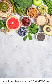 Superfoods on light stone background. Organic food and healthy vegan food. Legumes, nuts, seeds, avocado and green peas, asparagus. Top view copy space.