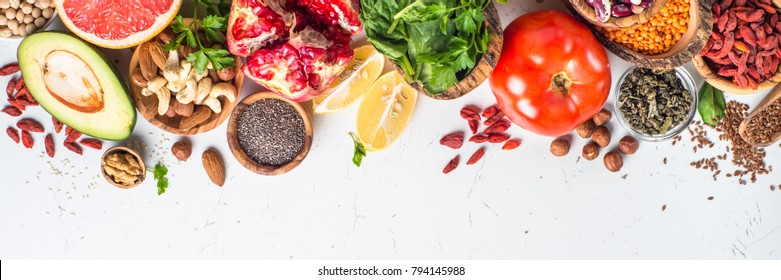 Superfoods on white background. Organic food and healthy vegan food. Legumes,  nuts, seeds, greens, oil and vegetables. Long banner format.
