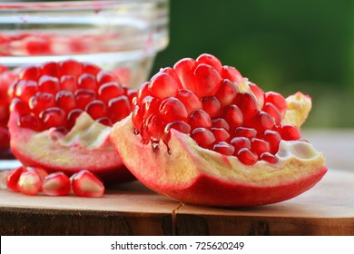 Superfruit, peeled pomegranate with red seeds against green nature background closeup (Punica granatum)