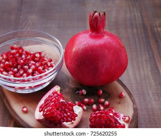 Superfruit, pomegranate fruit and seeds, one peeled and seeds in glass bowl,  (Punica granatum)