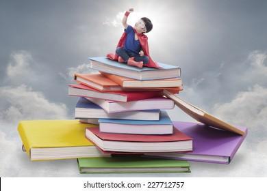 Superhero boy child sitting on pile of books