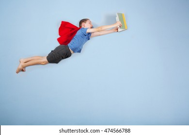 Superhero boy flying and reading a book