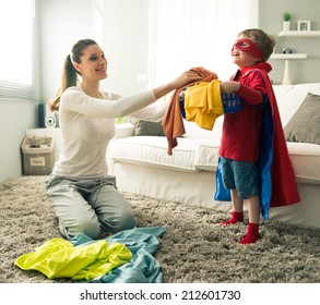 Superhero boy and his mother doing laundry together in the living room.
