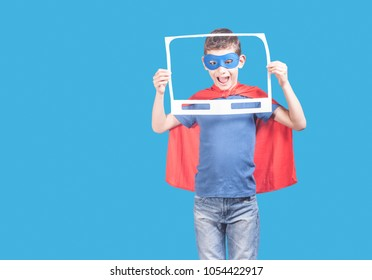 Superhero boy holding a paper TV frame. Action movies concept