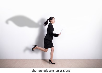 Superhero business woman running and hold laptop computer with white wall background, great for your design or text, asian