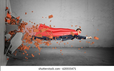A superhero businessman in a cape flying right through the wall leaving rubble behind him. Business achievements. Breakthrough. Obvious results.