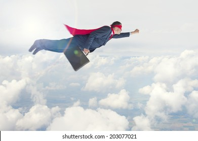 superhero businessman flying above the clouds