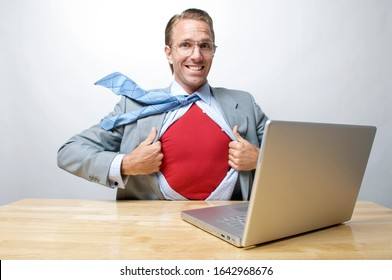 Superhero businessman smiling for the camera as he gets ready to save the day from his office desk