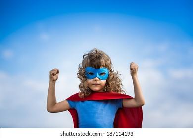 Superhero child against blue sky background. Kid, summer, super, hero, success, winner, business. Girl power and feminism concept