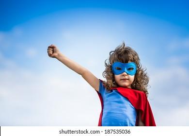 Superhero child against blue summer sky background. Kid having fun outdoors. Girl power and feminism concept