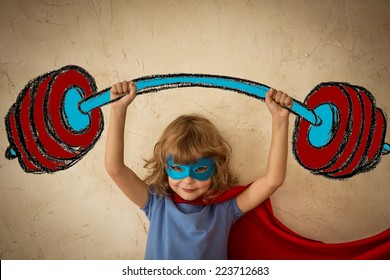 Superhero child against grunge wall background. Kid holding a drawn barbell. Success and winner concept