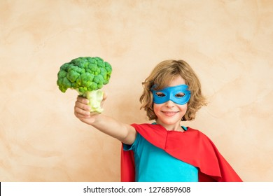 Superhero child eating superfood. Happy kid holding broccoli. Healthy eating and lifestyle concept. Green vegetarian food