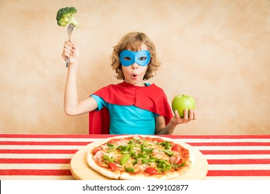 Superhero child eating superfood. Happy kid having lunch at home. Healthy eating and lifestyle concept. Green vegetarian food
