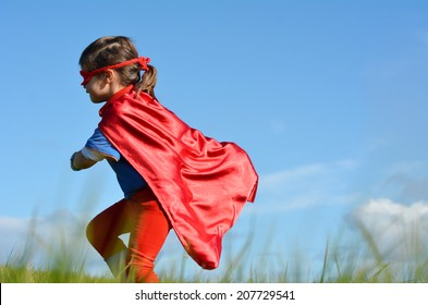 Superhero child girl running in a green field against blue sky background with copy space. concept photo of Super hero, girl power, play pretend, childhood, imagination. Real people. Copy space