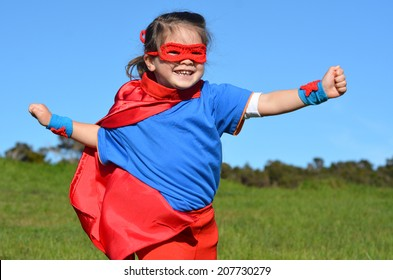 Superhero child (girl) runs against dramatic blue sky outdoor background with copy space. concept photo of Super hero, girl power, play pretend, childhood, imagination.
