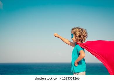 Superhero child on summer vacation. Super hero kid having fun on the beach. Active healthy lifestyle