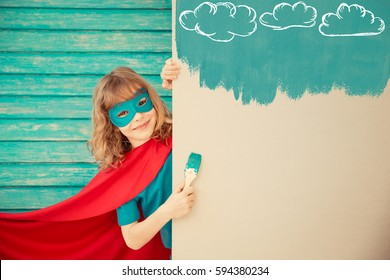 Superhero child painting the wall with blue color. Kid having fun at home. Spring renovation concept