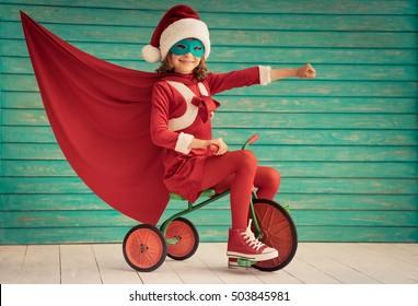 Superhero child rides a bike. Super hero kid playing at home. Christmas Xmas winter holiday concept