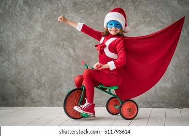 Superhero child rides a bike. Super hero kid playing at home. Christmas Xmas winter holiday concept