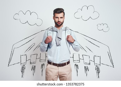 I am superhero. Confident and handsome man wearing a drawn flying cape while standing against grey background with illustration of the clouds on it.