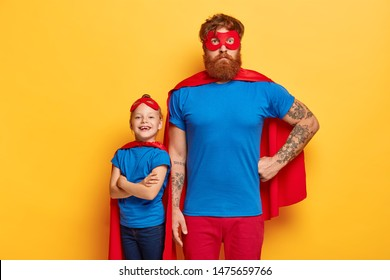 Superhero family. Powerful dad keeps one hand on waist, little child with arms crossed stands back, wear red capes, masks, ready for doing good things, isolated on yellow background. Colorful costumes