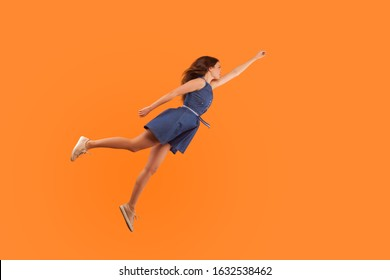 Superhero. Full length of confident motivated brunette woman in denim dress flying in air like hero and feeling superpower, striving up for success, reaching goal. studio shot orange background