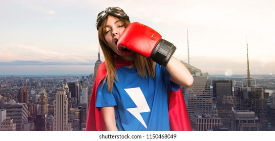 Superhero girl with boxing gloves giving a punch in a skyscraper city