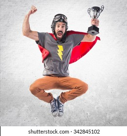 Superhero holding a trophy