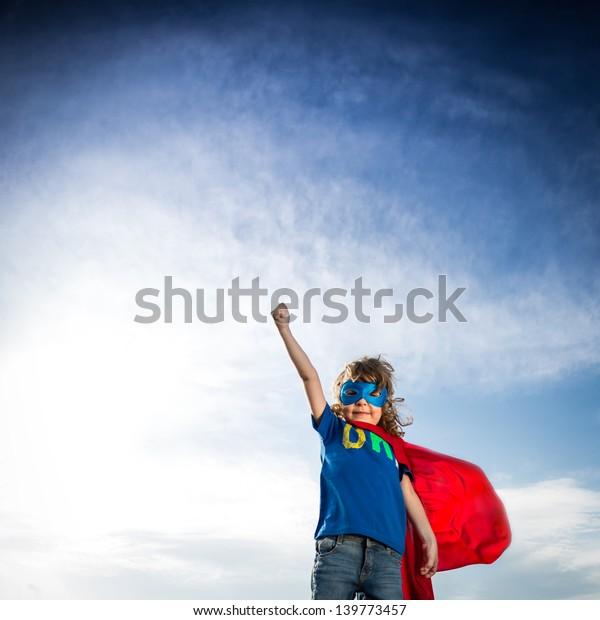 Superheld-Kind auf dramatisch blauem Hintergrund