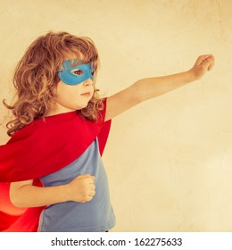 Superhero kid against grunge wall background