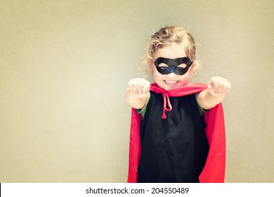 Superhero kid against textured wall background. playing activity concept. homemade costume. toned image.