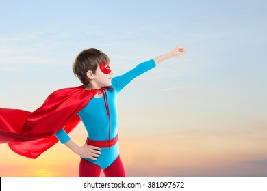Superhero kid flying on sunset sky background. Power concept.
