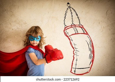 Superhero kid in red boxing gloves. Child punching on the drawn bag. Winner and success concept