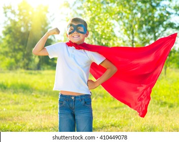 Superhero Kid Showing his Muscles over nature background. Little boy wearing superhero costume and having fun outdoors