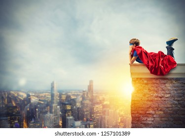 Superhero kid sitting on a wall that dreams