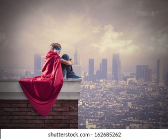 Superhero kid sitting on a wall that controls the city