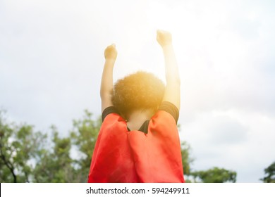 Superhero leader kid raising two hands up in the sky - success and winning achievement concept