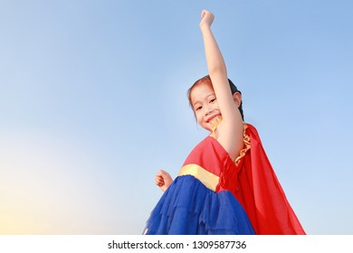 Superhero little girl in stance to fly on sky background at sunset light. Kid super hero concept.