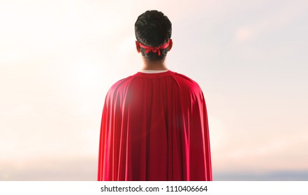 Superhero man with mask and red cape in back position on a sunset background