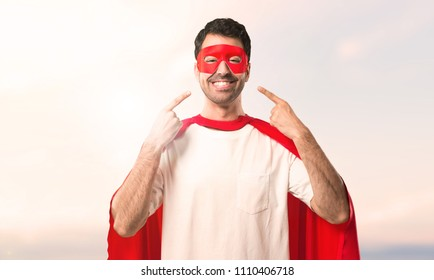 Superhero man with mask and red cape smiling with a happy and pleasant expression while pointing mouth and face with fingers on a sunset background