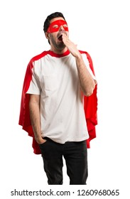 Superhero man with mask and red cape yawning and covering wide open mouth with hand. Sleepy expression on isolated white background
