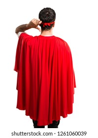 Superhero man with mask and red cape on back position looking back while scratching head on isolated white background
