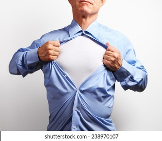 Superhero. Mature businessman tearing his shirt off over white background