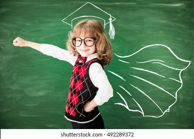 Superhero school child in class. Happy kid against green blackboard. Knowledge is power concept