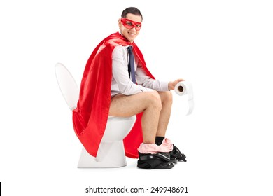 Superhero sitting on a toilet and holding a toilet paper roll isolated on white background
