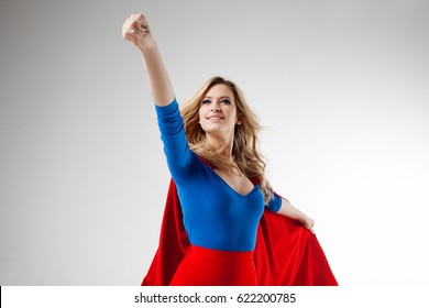 Superhero Woman. Young and beautiful blonde in image of superheroine in red Cape growing. Onward and upward